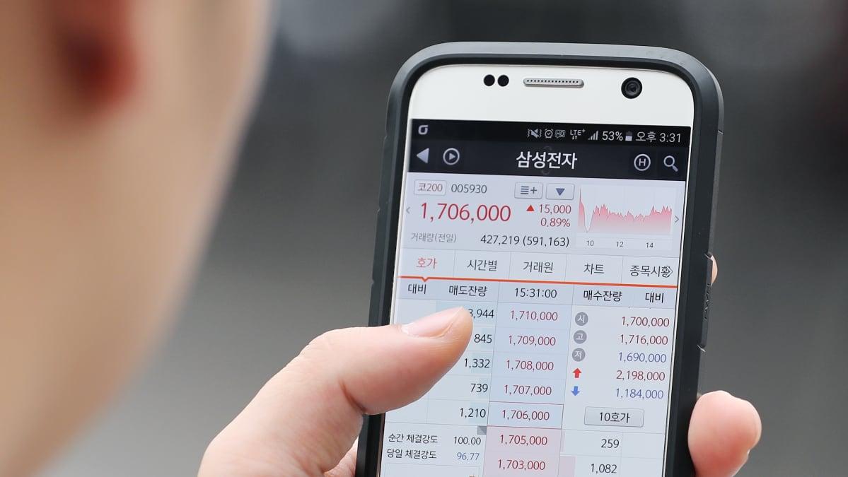 Eteläkorealainen mies tutkii osakekursseja puhelimestaan Soulissa