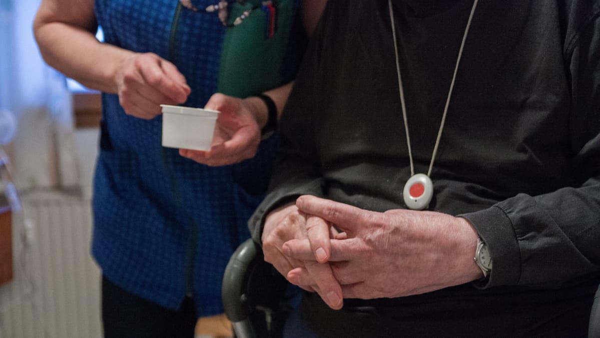 Kotihoitaja antaa vanhukselle lääkettä.
