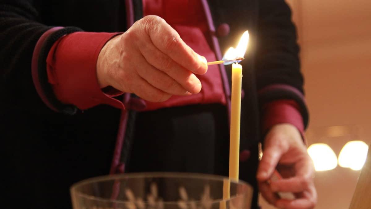 Piispa sytyttää kynttilän.