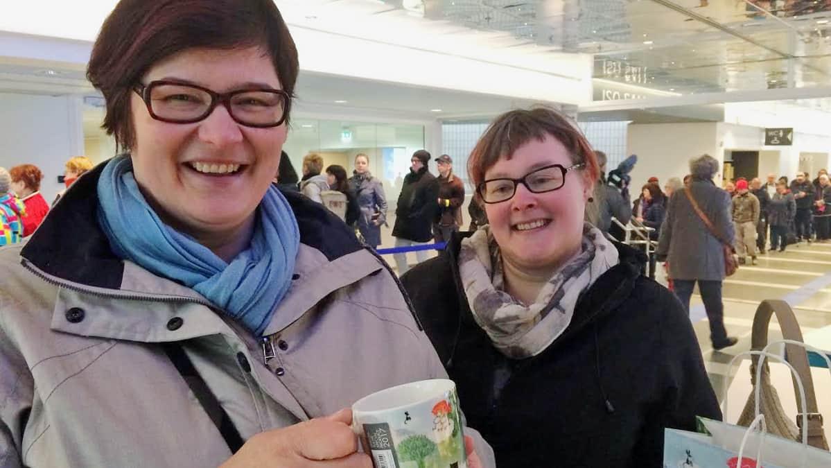 Tampere-talon aulassa kaksi hymyilevaa naista, joista toisella on uusi muumimuki kädessään