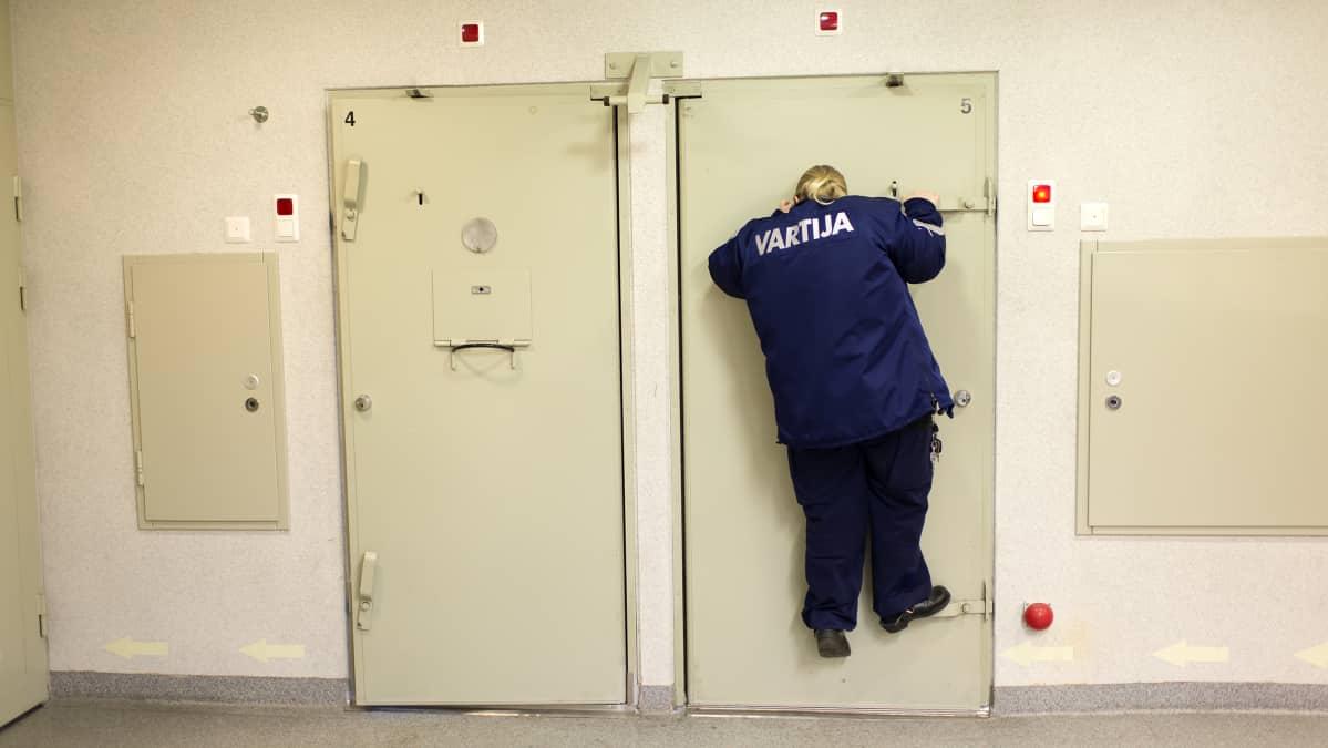Kokkolan poliisivankilan vartija Ulpu Keränen kurkkaa selliin ovisilmästä.