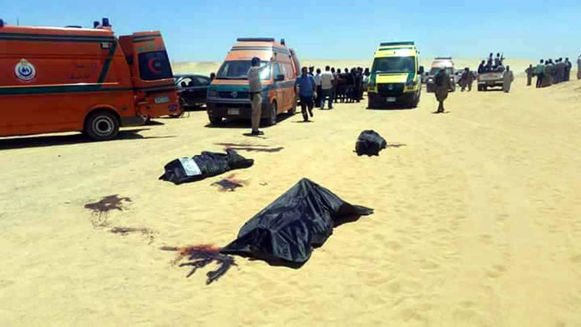 Pelastus- ja muita ajoneuvoja, joiden luona on ihmisiä. Etualalla peitettyjä ruumiita.