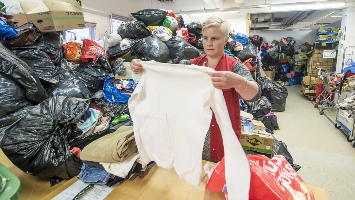 Eila Ikäheimo tarkastaa vaatteiden kuntoa.