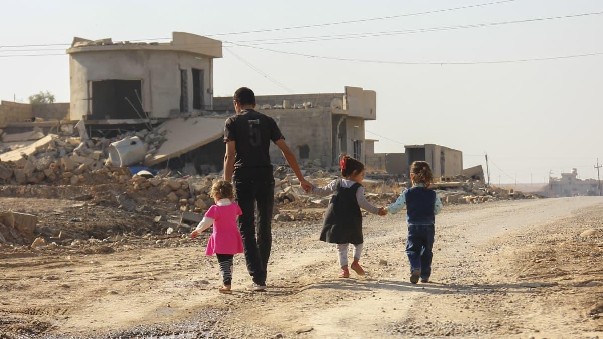 perhe kävelee raunioilla