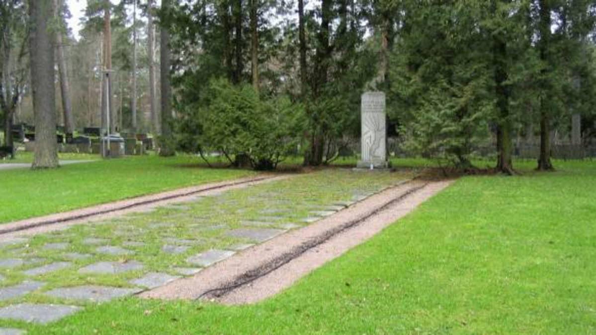 Muistomerkki hautausmaalla, puiden katveessa.