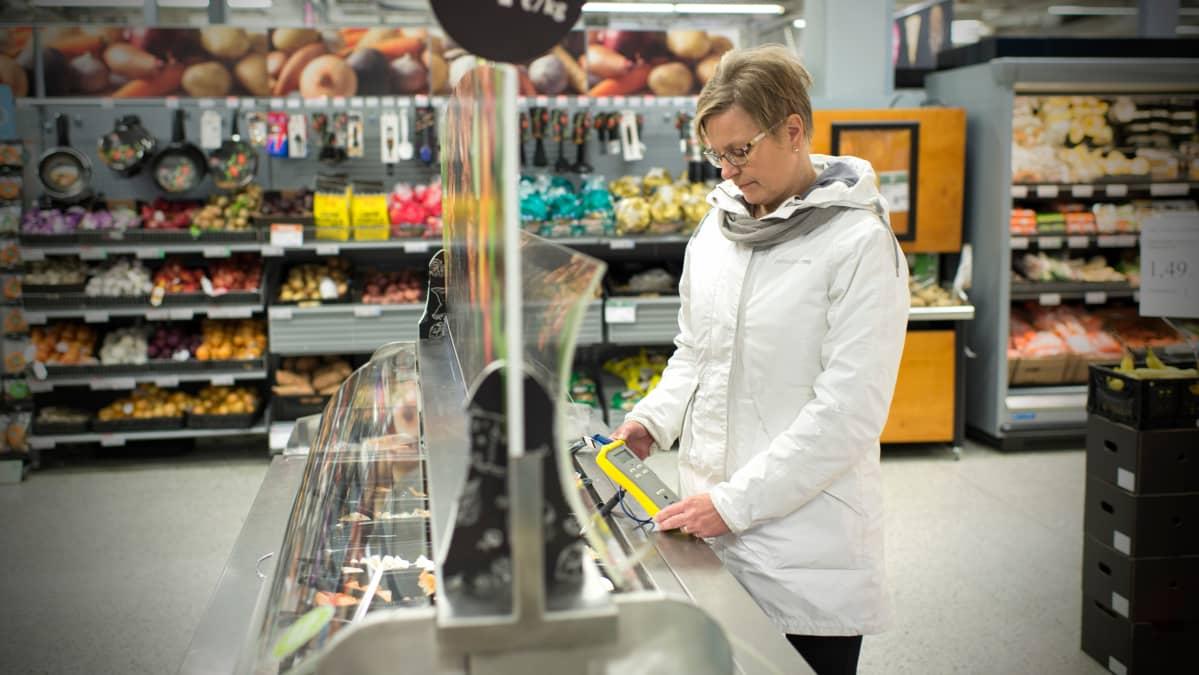 Terveystarkastaja mittaa salaattibaarin lämpötilaa.