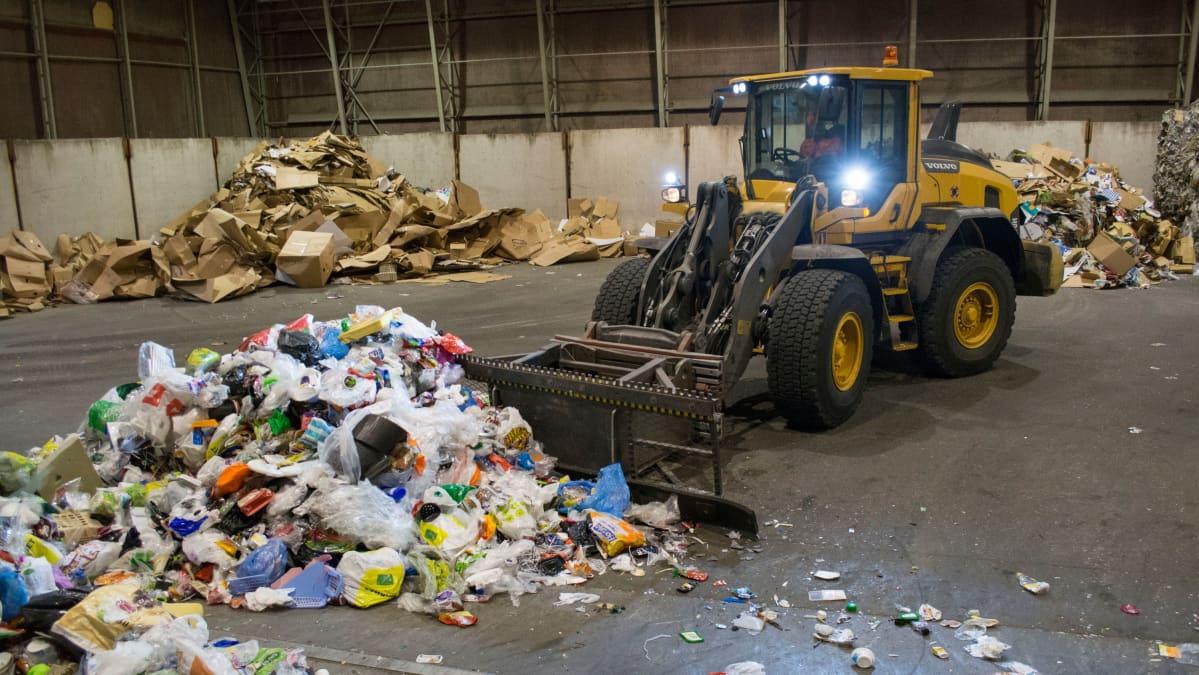 Kauhakuormaaja työntää muovipakkauksia paalauskoneen hihnalle