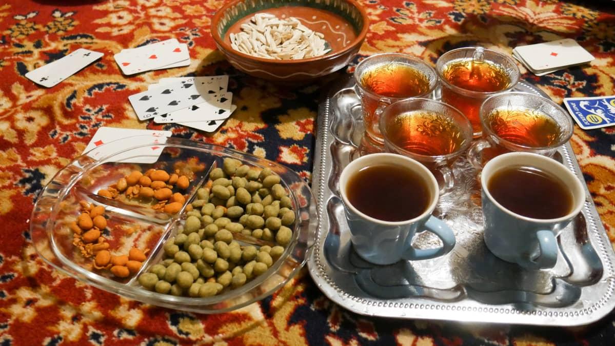 Kuvassa itämaisella matolla teekuppeja, pelikortit ja pähkinöitä