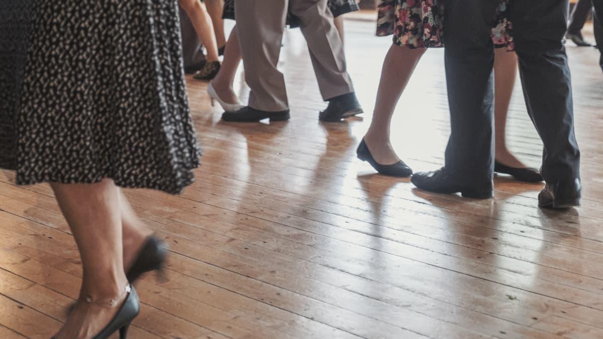 Tanssivien parien jalkoja, parkettilattia.