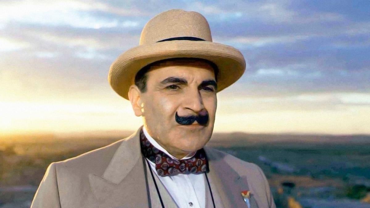 Hercule Poirot seisoo ilta-auringossa mietteliäänä olkihattu päässään.