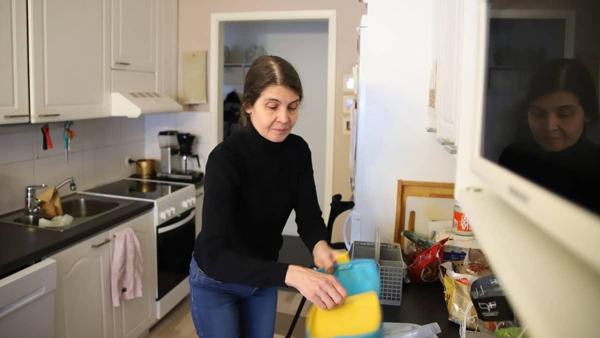Joensuulainen Satu Lamminsalo tyhjentää puhtaita astioita tiskikoneesta.