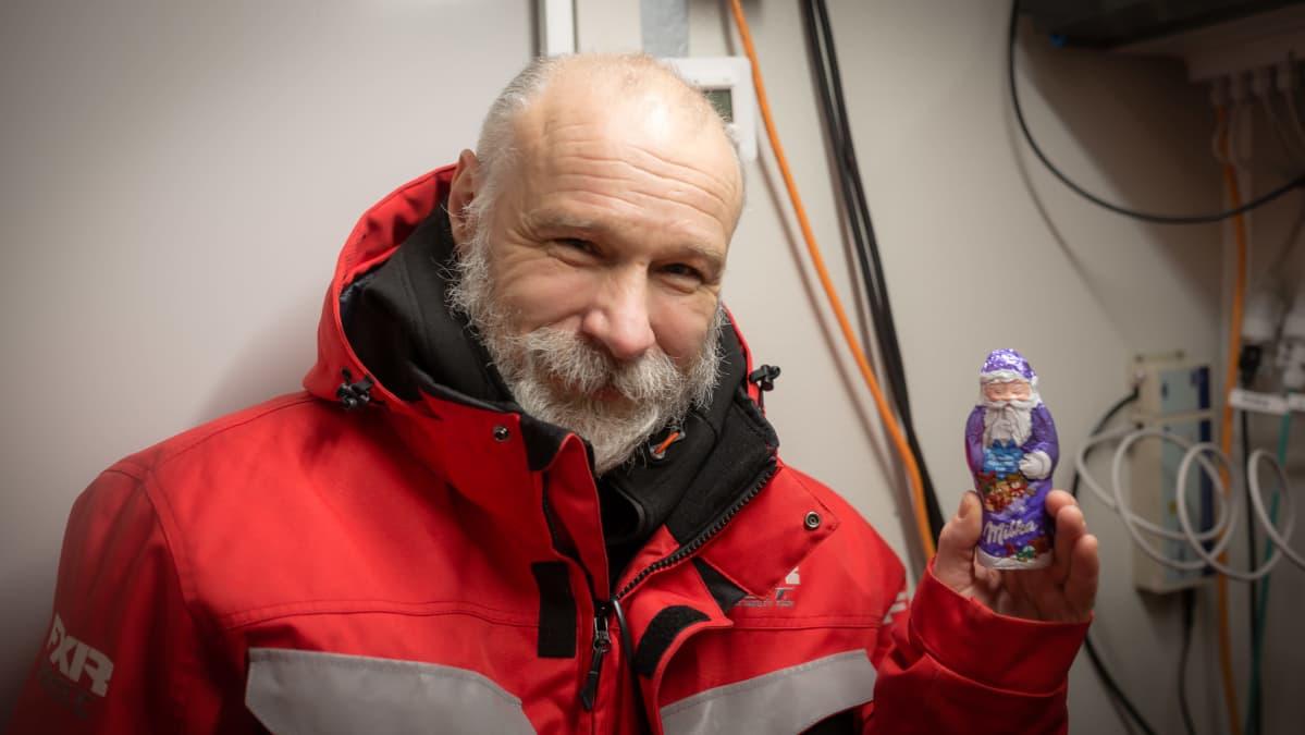 Hymyilevä partainen Jari Haapala pitelee kädessään suklaista joulupukkia.