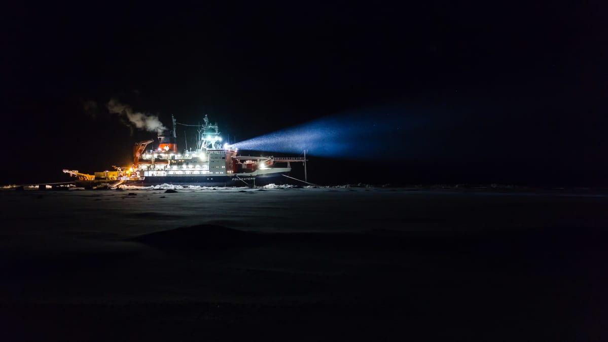 Tutkimuksen aluksen valot loistavat pilkkopimeässä.