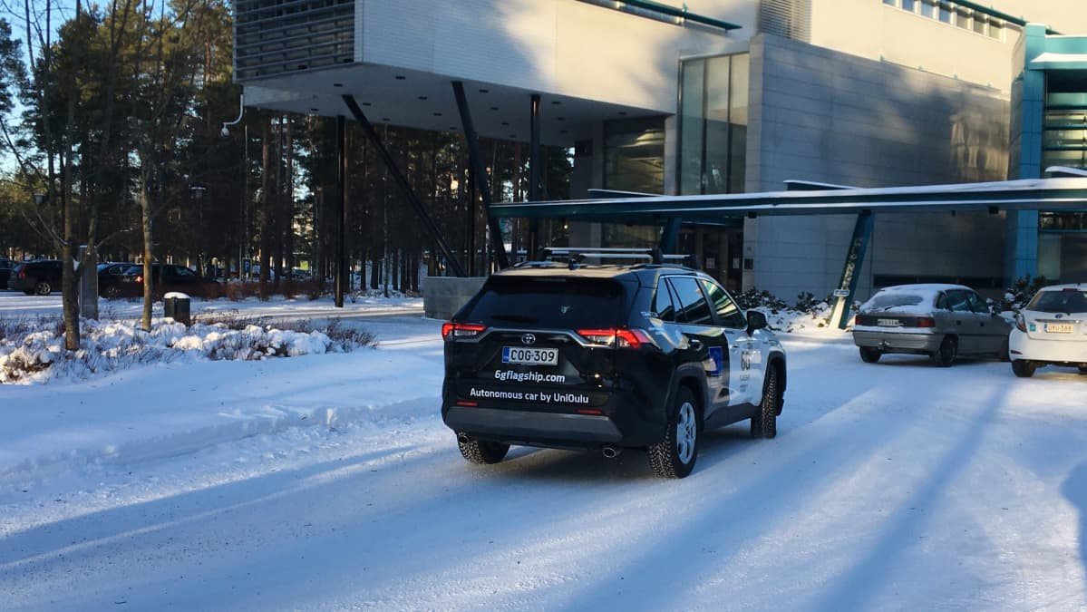 Oulun yliopiston 6G testiauto yliopiston päärakennuksen edessä.