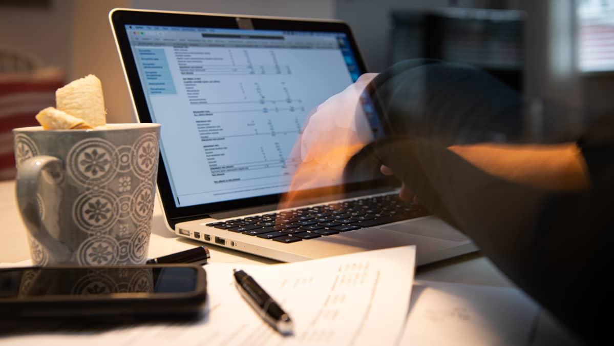 Nainen työskentelee etänä kannettavalla tietokoneella.