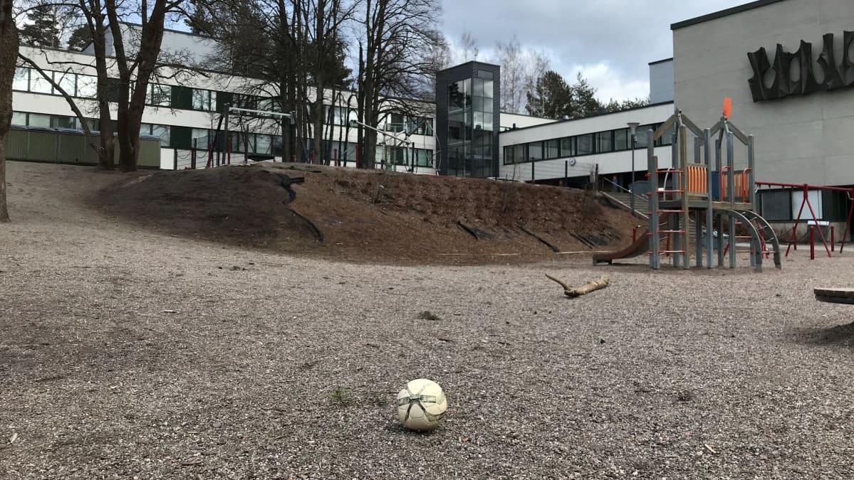 Koulun piha on tyhjä oppilaista. Pihalla on yksinäinen pallo.