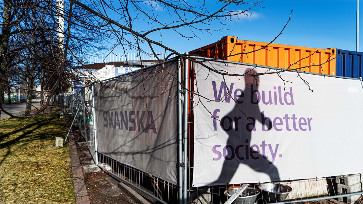 """Skanskan mainosteksti rakennustyömaalla: """"We build for a better society""""."""