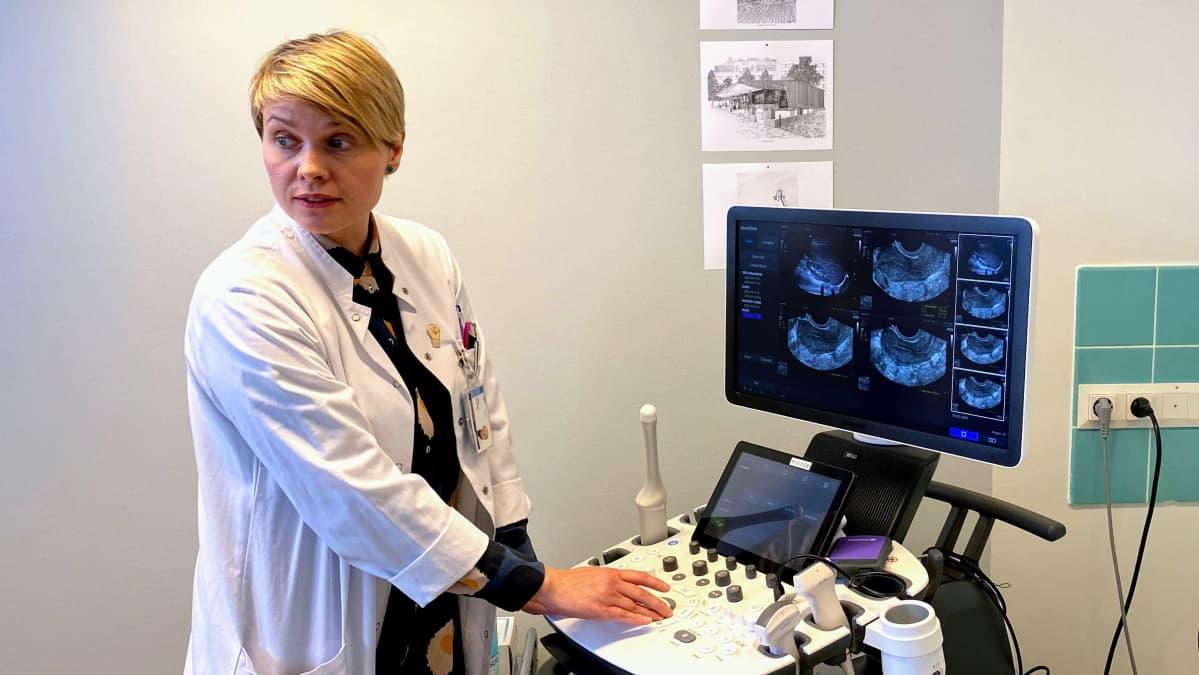 Professori Terhi Piltonen käyttää ultraäänitutkimuslaitetta