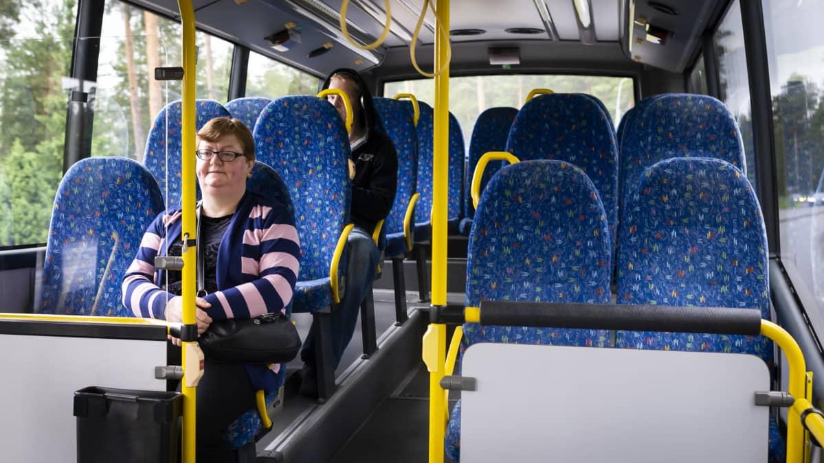 Ihmisiä liikkuvassa linja-autossa.