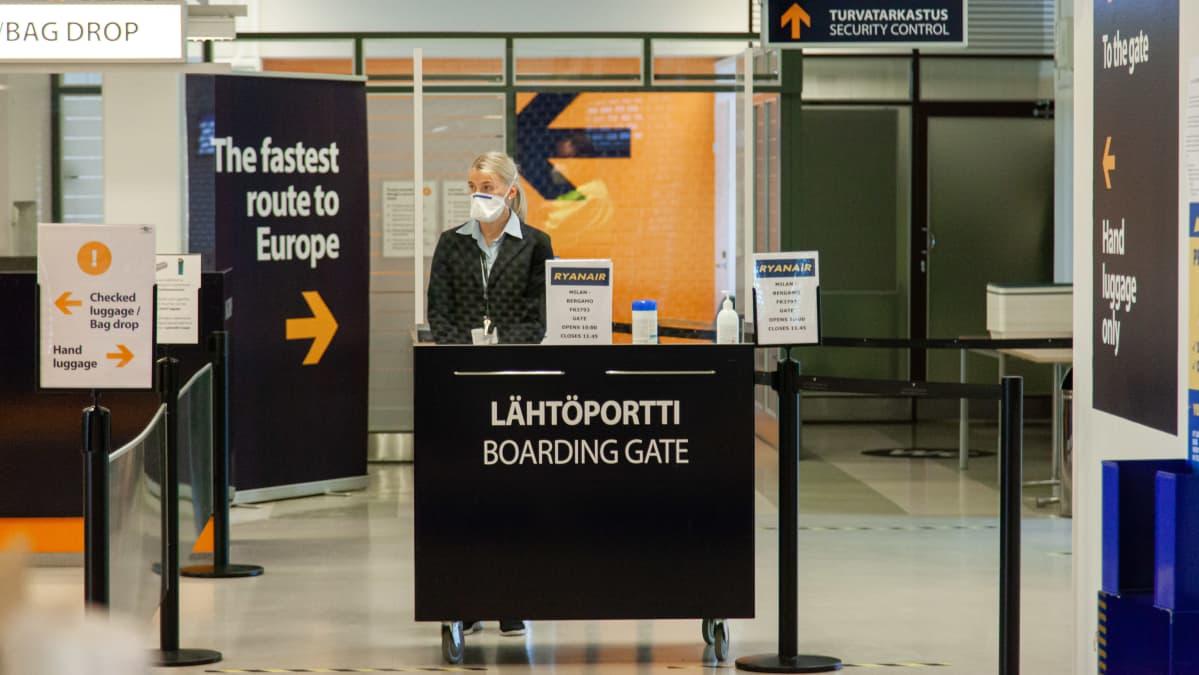 Lappeenrannan lentoaseman lähtöportti koronaviruksen aikaan. Työntekijällä hengityssuojaimet ja kumihanskat.
