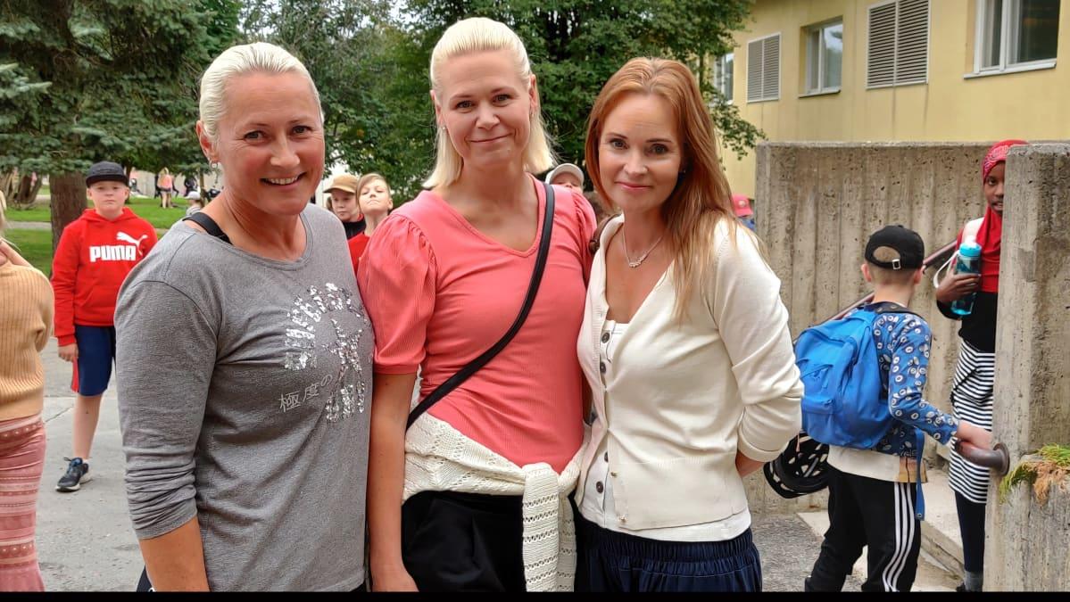 Kolme naistaa seisoo koulun pihalla ja poseeraa.