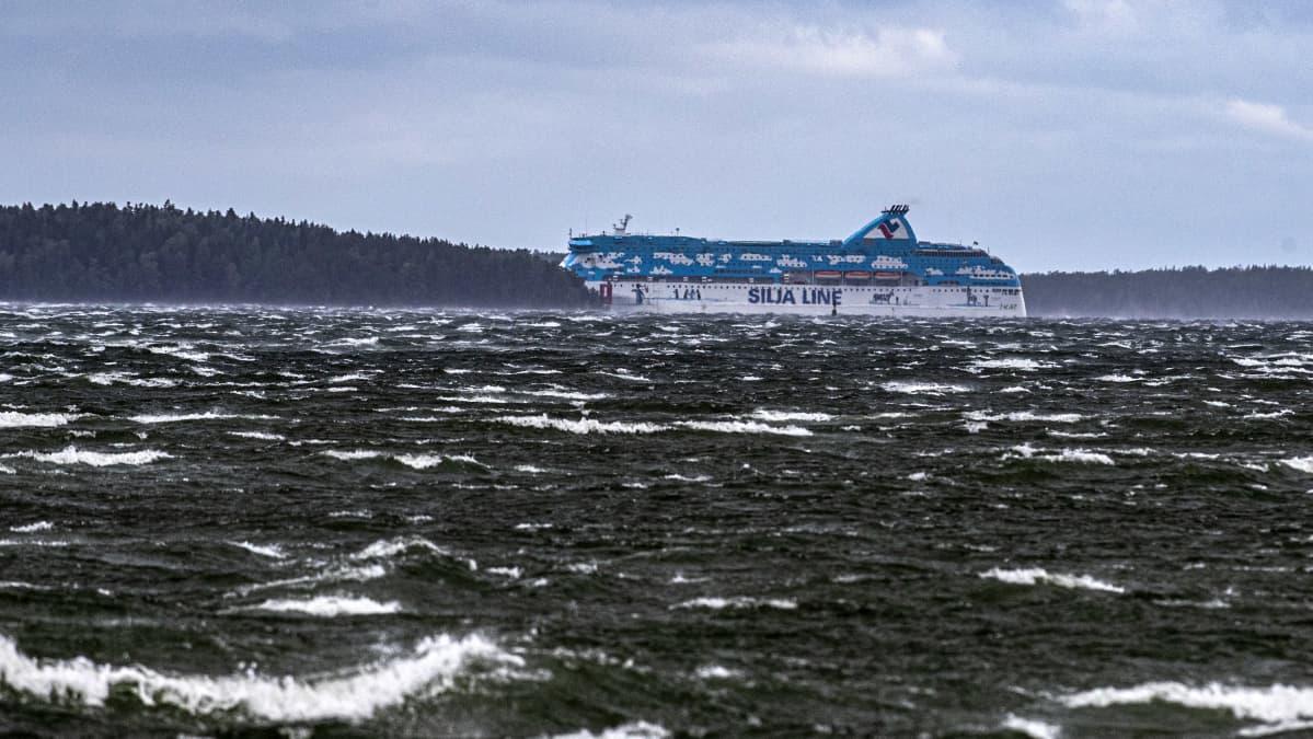 Tallink Siljas blåvita passagerarfartyg Galaxy försvinner bakom en ö under en höststorm med vita toppar på vågorna.