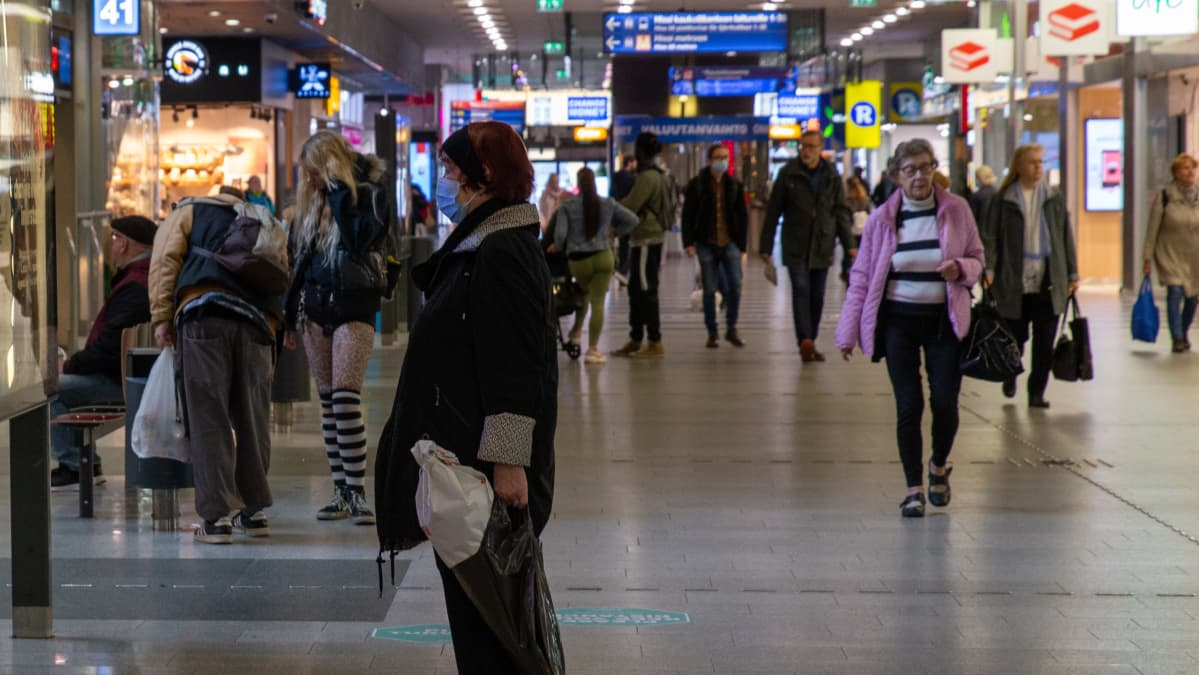 Kampin paikallisliikenteen terminaalissa kulkee ihmisiä.