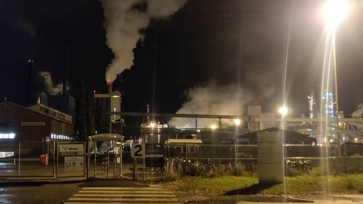 Metsäfibren tehtaan portti, takana näkyy savua