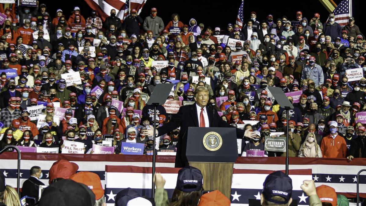Presidentti Trump puhuu suuressa vaalitilaisuudessa, taustalla näkyy iso joukko kannattajia.