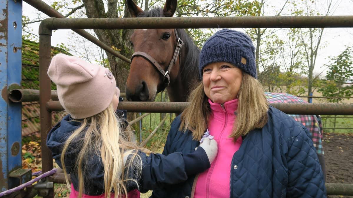Uudenmaan hevosenomistajien yhdistyksen puheenjohtaja Birgitta Mangström hevosensa Konosen aitauksen vieressä.