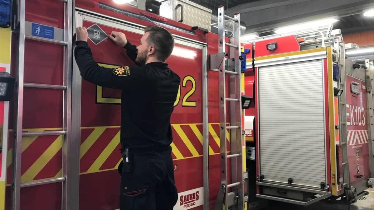 Palomies Eemil Laakkonen liimasi tarran Etelä-karjalan pelastuslaitoksen uusimpaan autoon.