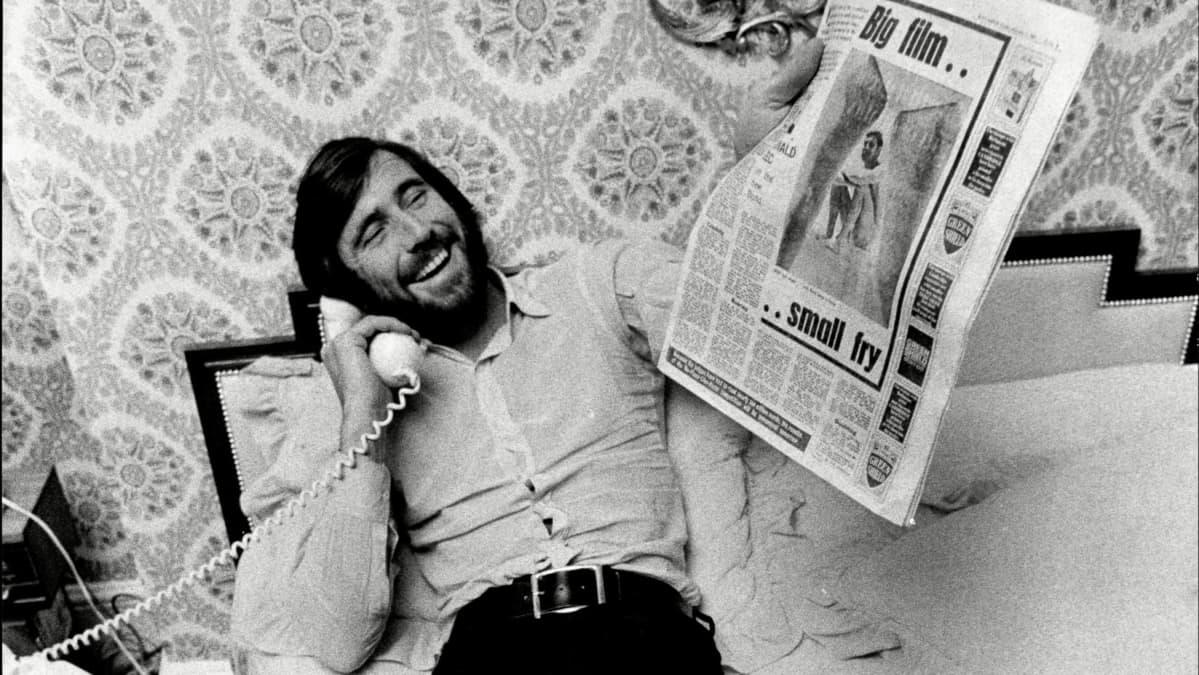 George Lazenby vanhassa valokuvassa, puhelin kädessä ja sanomalehti toisessa. Kuva dokumentista Becoming Bond.