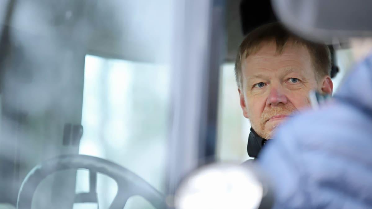 Maatalousyrittäjä Jari Sippola traktorin hytissä.