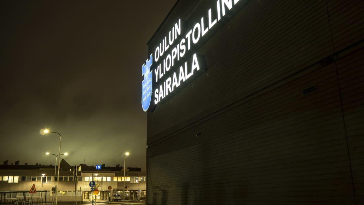 Oulun yliopistollisen sairaalan valologo seinässä. Taustalla vanha sairaala iltavalaistuksessa.