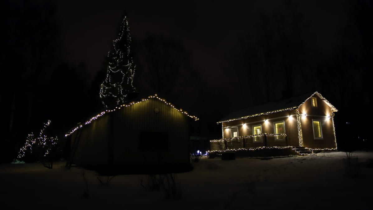 Mikkelin Emolassa sijaitseva, jouluvaloin koristeltu talo ja korkea kuusi.