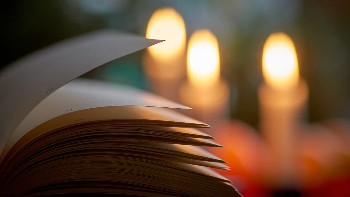 Kirja kynttilän valossa.