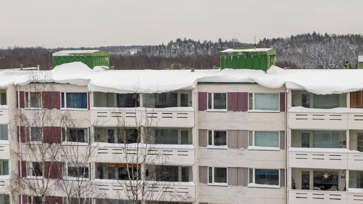 Kerrostalon katon reunalla näkyy valtavia lumikinoksia.