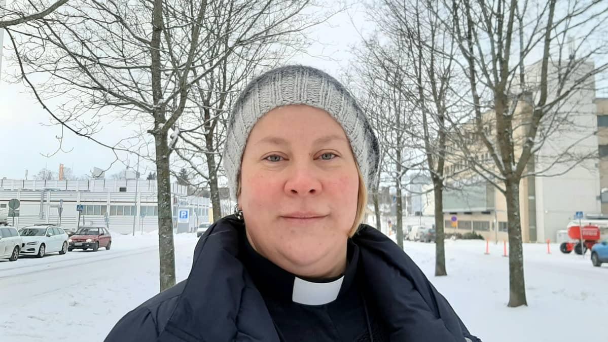 Nainen katsoo kameraan talvimaisemassa. Hänellä on kaulassa evankelisluterilaisen papin liperit.