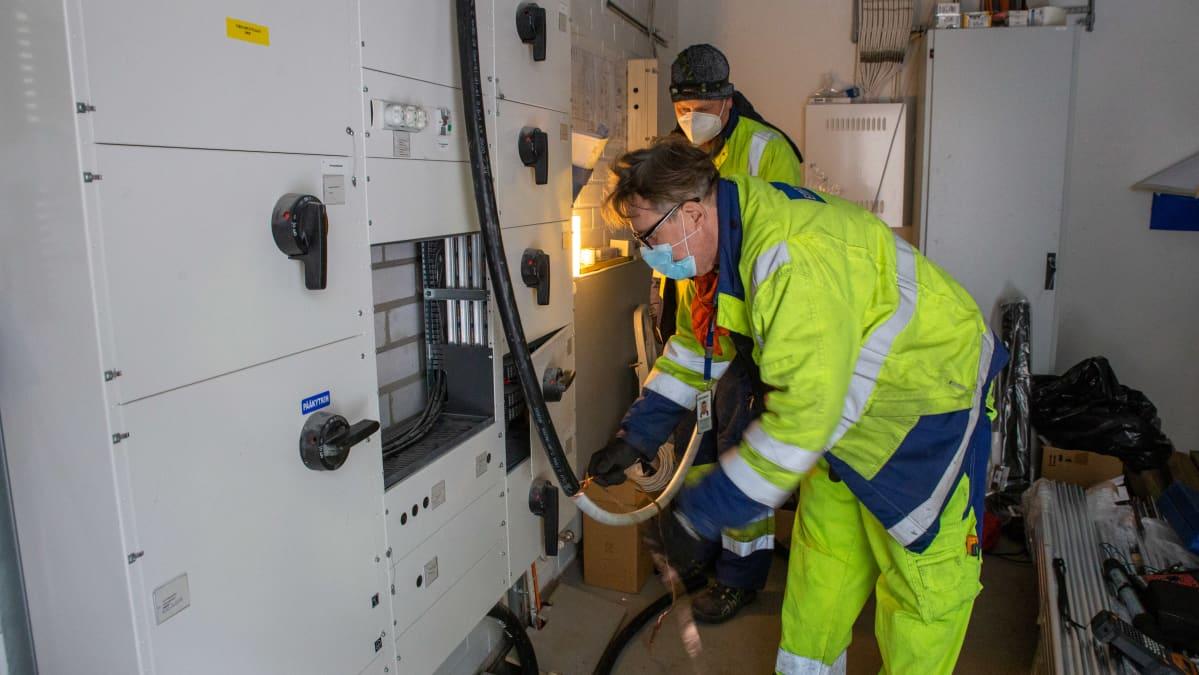 Enersensen työntekijät Matti Tapanainen ja Petri Leander asentavat sähköautojen latauskeskuksen syöttökaapelia talon pääsähkökeskukseen.