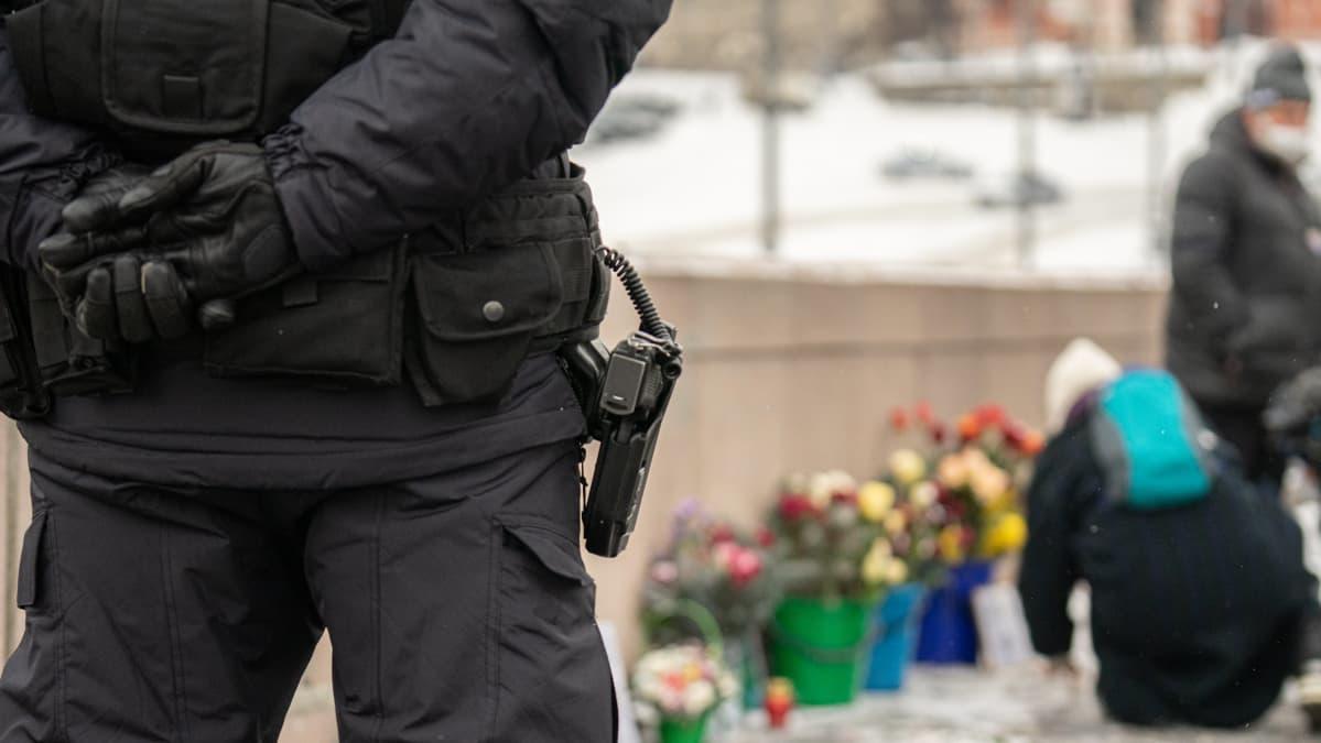 Poliisi seisoo etualalla. Kuvassa näkyy hänen vyöllään oleva pistooli. Kauempana näkyy Nemtsovin muistopaikka, jonne ihmiset tuovat kukkia.