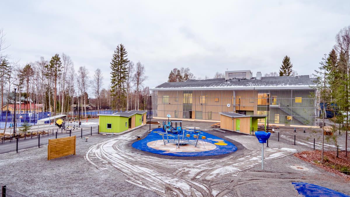 Juuri valmistuneen koulun piha. Kuvan etualalla leikkitelineitä.