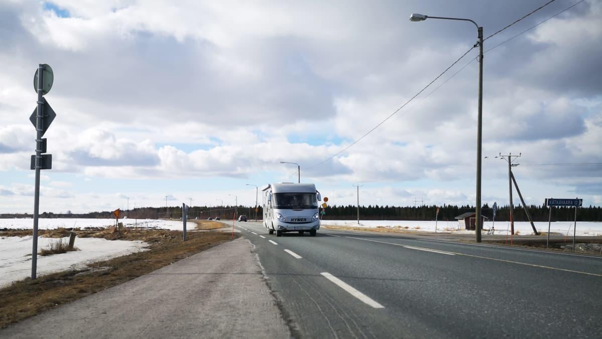 Matkailuauto lähestyy sulaa asvalttitietä pitkin, ympärillä näkyy lumisia peltoja.