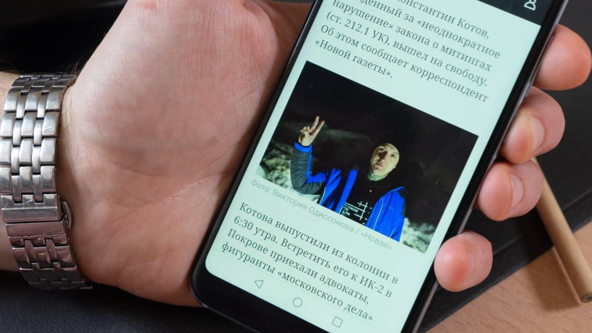 Mies näyttää valokuvaa matkapuhelimen ruudulta.