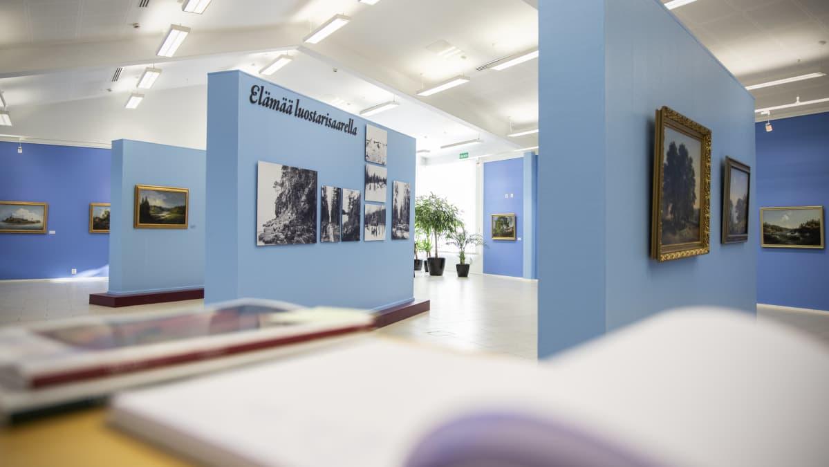 Maalauksia ja valokuvia näyttelyssä Valamon luostarin kulttuurikeskuksessa.