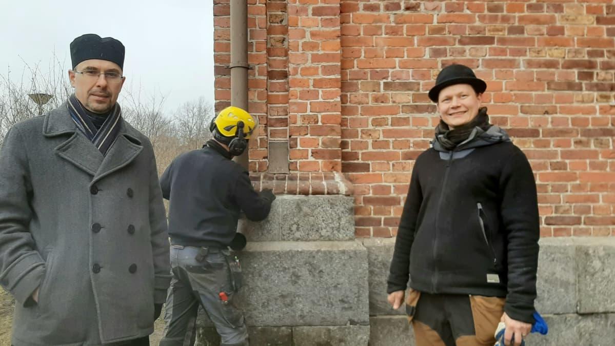Isä Andrei Sotsov (vasemmalla) ja rakennusentisöijä Leo Lönnroth, takana korjaustöitä tekee Eddie Österåker
