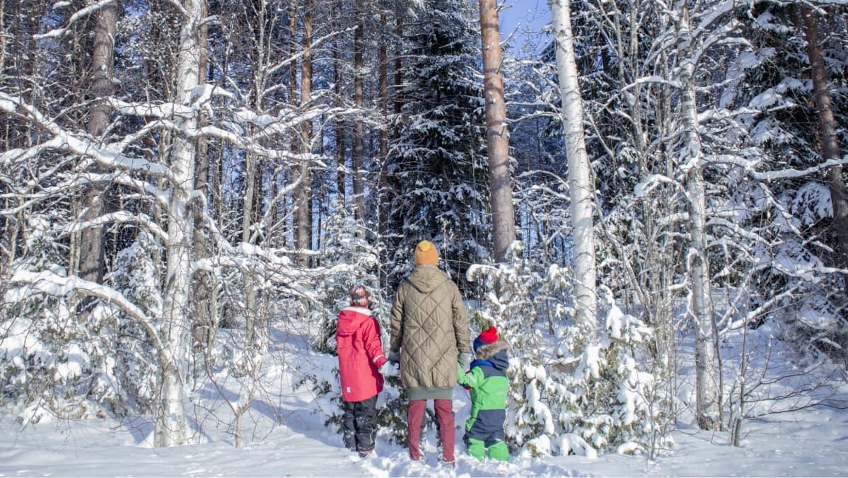 Äiti ja kaksi lasta seisovat metsän reunassa