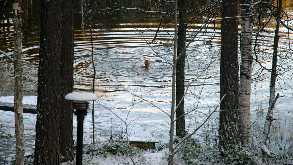 Mies ui talvisessa järvessä