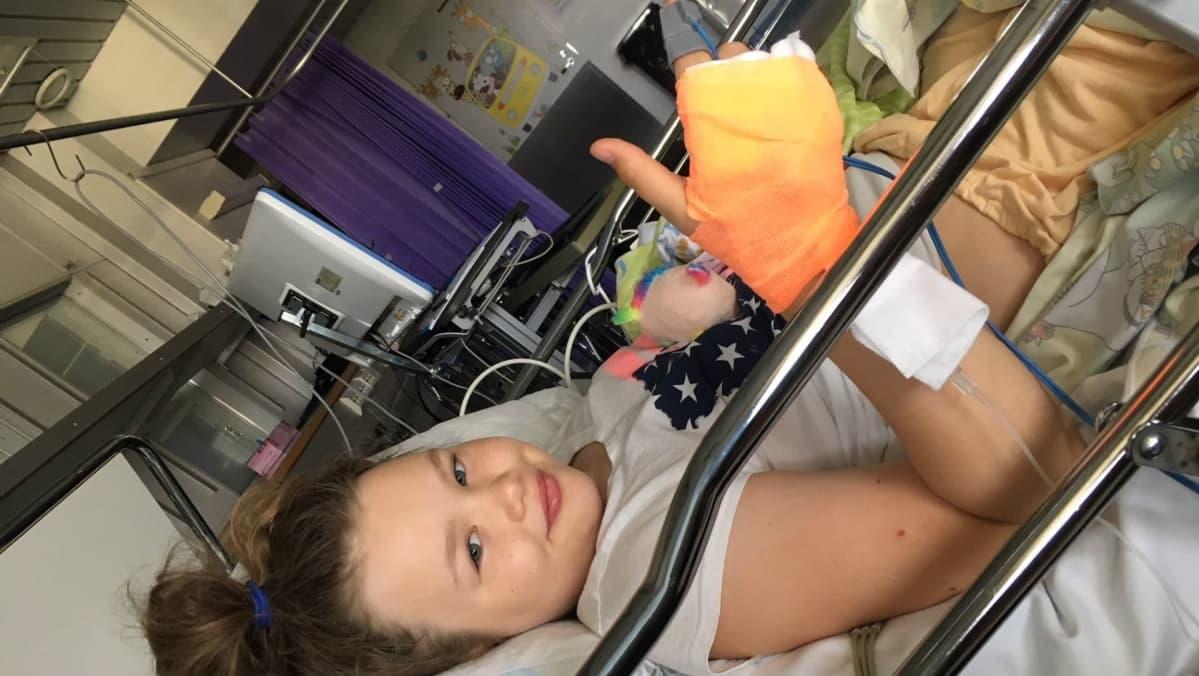 tyttö makaa sairaalan sängyssä