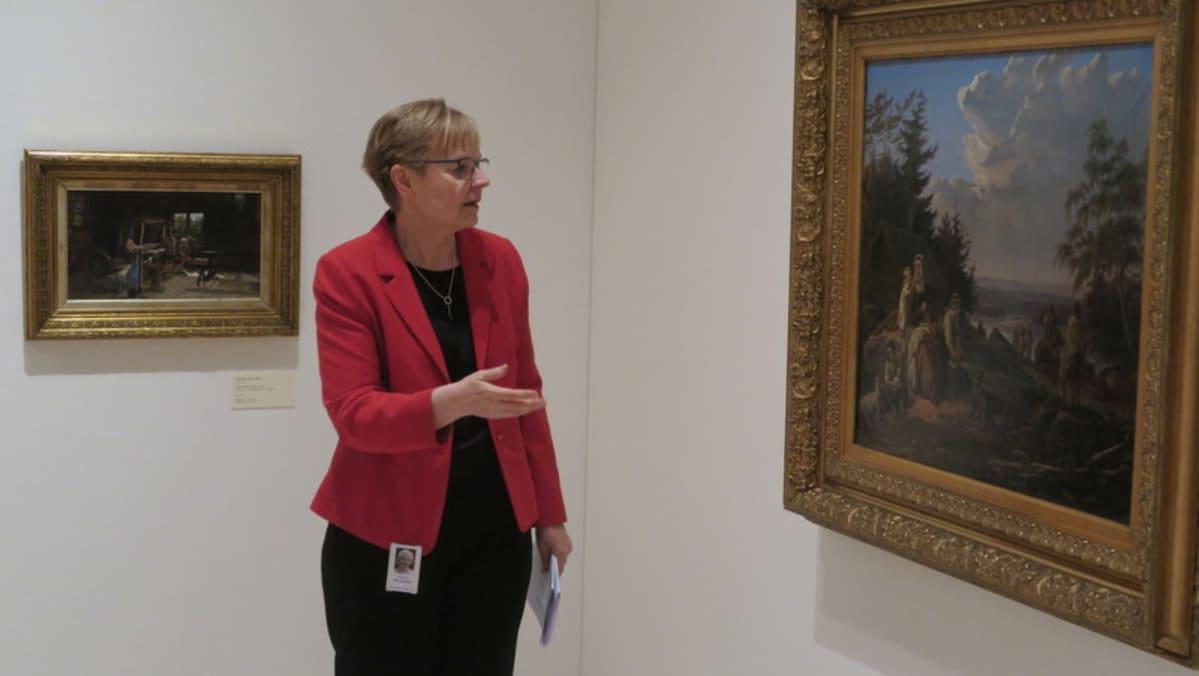 Nainen esittelee maalausta
