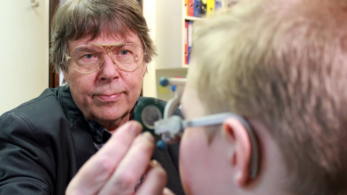 Optikko Raimo Laitinen tarkastaa nuoren näköä.